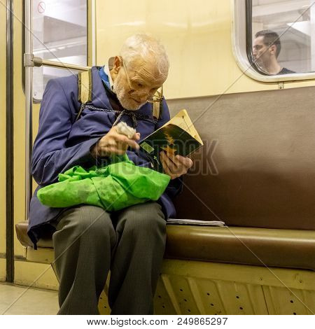 Moscow, Russia - July 15, 2018: Elderly, Poor, Lonely Man In Broken Glasses Enthusiastically Reading