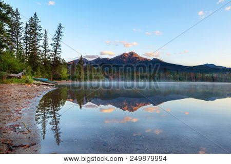 Golden Sunrise Breaks Out Over Pyramid Mountain And Low Fog Settles On The Surface Of Edith Lake In