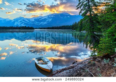 Morning Sun Breaks Out Over The Rocky Mountains At Edith Lake In Jasper National Park, With A Boat I