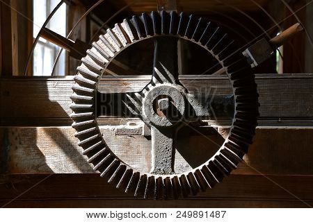 An Old Heavy Cast Iron Gear And Wooden Support Beams Receive Stream Of Sunlight From A Window In An