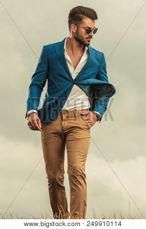 relaxed man in blue suit and wearing sunglasses walking on a windy weather and looking down to side, on a cloudy background