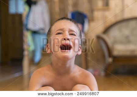 Little Boy Sitting On The Floor, He's Upset And Crying. The Child Is Crying Sitting On The Floor In