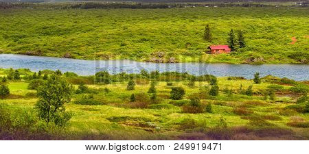 Small Red Bulding In Iceland Landscape Next To River