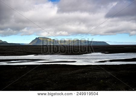 An Icelandic Landscape Of Black Sand And Distant Mountains With In The Fore Ground A River