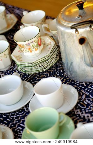 Stacks Of China Tea Cups And Saucers And A Metal Kettle