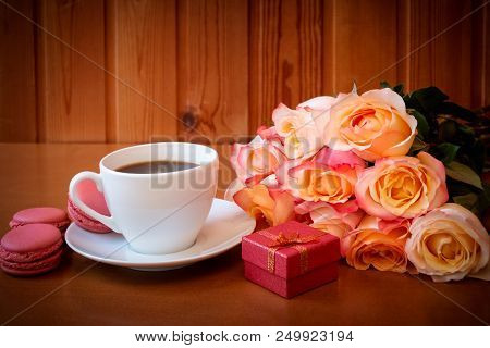 Cup Of Coffee, Bouquet Of Pink Roses Flowers And Red Gift Box. Selective Focus. Place For Text.