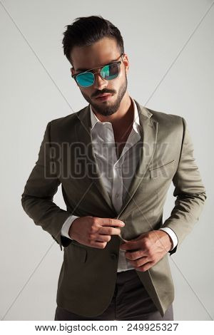 portrait of sexy man with sunglasses and green suit standing on light grey background, buttoning his suit