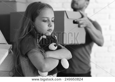 Kid And Guy Move In Or Move Out. Daughter Hugs Teddy Bear And Father Holds Box. Girl With Sad Face A