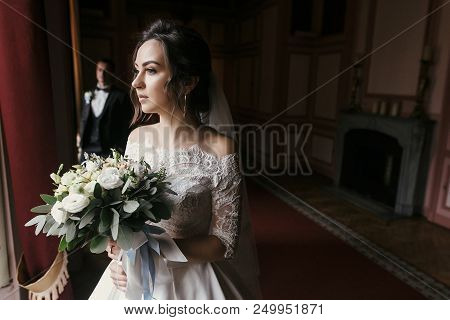 Gorgeous Bride In Amazing Dress With Bouquet And Stylish Groom Posing At Window In Luxury Room In Ho
