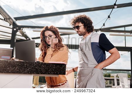 Joining Wife. Curly Dark-haired Man Wearing Sunglasses Joining Her Wife At Work While Sitting In The