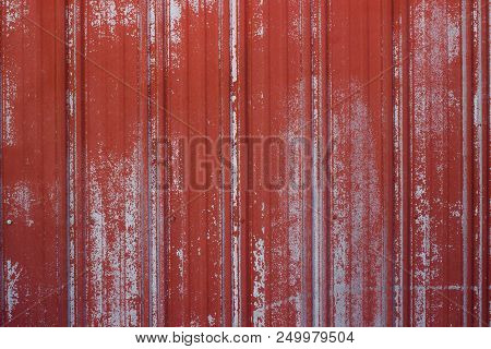 Grooved And Ridged Rusted Metal Surface With Faded Red Paint