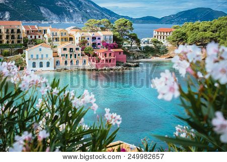 White And Lilac Flower Blossom In Front Of Turquoise Colored Bay In Mediterranean Sea And Beautiful