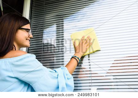 Girl Or Young Woman Cleaning White Pvc Window With With Jalousie