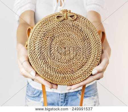 Fashionable Round Female Bag Made Of Natural Rattan Material In The Hands Of A Young Girl Against A