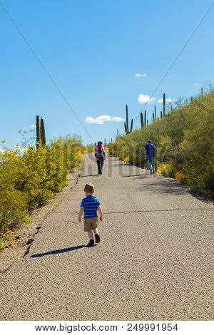 Three Generations, A Grandfather, Father, And Two Children, Hike Up The Paved Path Of A Desert Mount