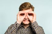 funny ludicrous joyful comic playful man pretending to look through binoculars. portrait of a young guy on light background. emotion facial expression. feelings and people reaction. poster
