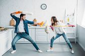 couple having fun and pretending fight with cleaning tools in kitchen poster