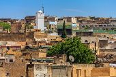 View over the ancient yellow clay and stone brick rooftops of the Fes medina with a mosque in the background poster