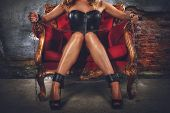 Sensual provocation of a sexy bdsm woman in lingerie on an armchair poster
