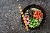 Hawaiian salmon fish poke bowl with rice, radish,cucumber, tomato, sesame seeds and seaweeds. Buddha bowl. Diet food. Top view. Flat lay poster