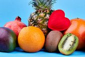 Set of colorful tropical fuits. Fresh exotic fruits placed on a blue wooden surface. Nutritious ingredients for healthy diet. poster