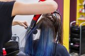 Professional hairdresser, stylist drying client hair with blow-dryer at salon, studio. Beauty and haircare concept poster
