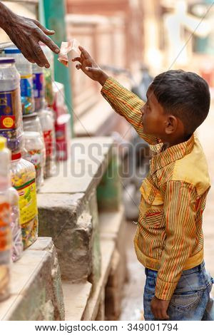 VARANASI, INDIA, JANUARY 20, 2019 : A young boy is giving money to the street shop seller in a narrow street of Varanasi