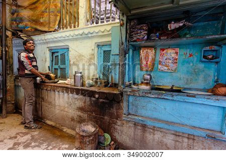VARANASI, INDIA, JANUARY 19, 2019 : An Indian chef is working in his colorful outdoor kitchen in a narrow street of Varanasi.