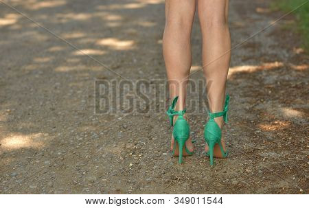 Beautiful Tanned Girl Legs In High Heels. Slender Female Legs Are Dressed In Green Sandals With Heel