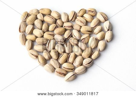 Heart Shaped Pile Of Tasty Pistachios On White Background, Above View. Delicious Nuts In Shells. Org