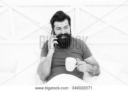 Hello Dear. Bearded Man Using Mobile Technology In Bed. Handsome Guy Talking On Phone And Drinking C