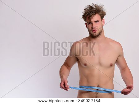 Athlete With Messy Hair Measures Waist Or Sixpacks