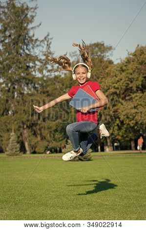 The Wise Choice For Audio Fanatics. Happy Child Jump On Green Grass. Small Girl Listen To Audio Book