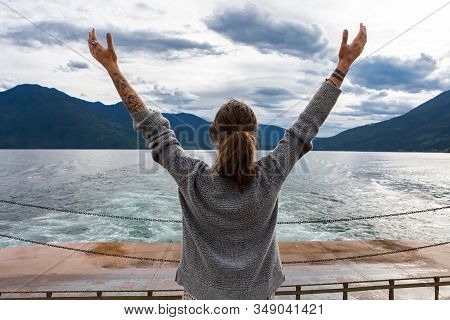 Close Up From Behind Of A Young Lady On The Deck Of A Passenger Ferryboat. Arms Raised In Enthusiast