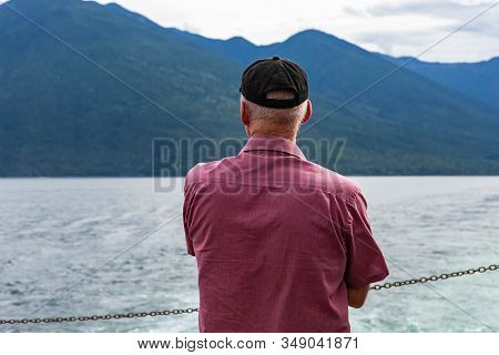 Close Up From Behind Of A Man On The Deck Of A Passenger Ferryboat. Looking Slightly Towards Left At