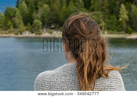 Close Up Shot From Behind Of Head And Shoulders Of A Young Woman On A Ferryboat. The Woman Is Lookin