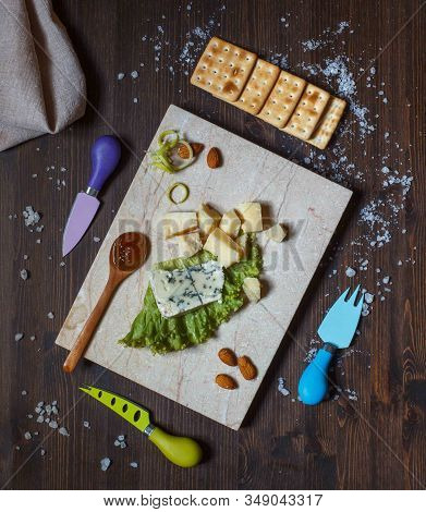 Parmesan And Roquefort On A Light Marble Board On A Dark Wooden Background With Knives For Cheese, V