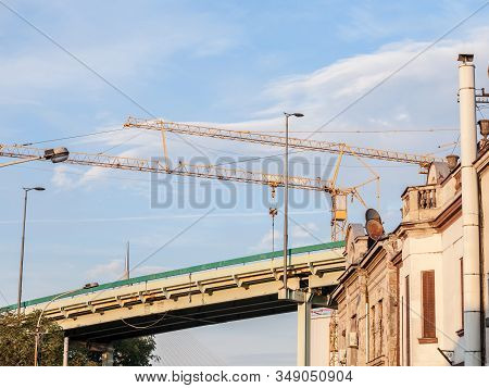 Peri Urban Scenery Of The Suburb Of Belgrade, With Cranes On A Construction Site Behind Old Houses S