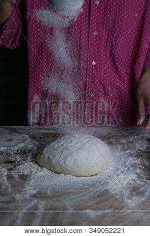 The Woman Sprinkles Flour Dough From The Fullness For Sifting Flour, Flour Falls On The Dough, A Bea