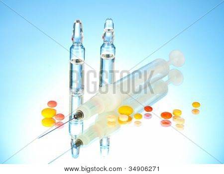 syringe monovet, ampoules and pills on blue background