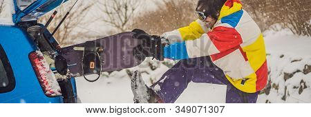 The Snowboard Does Not Fit Into The Car. A Snowboarder Is Trying To Stick A Snowboard Into A Car. Hu