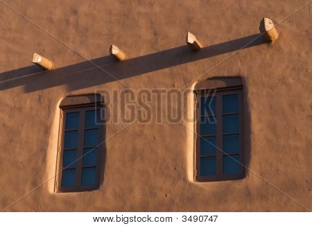 Adobe Wall With Windows At Dusk