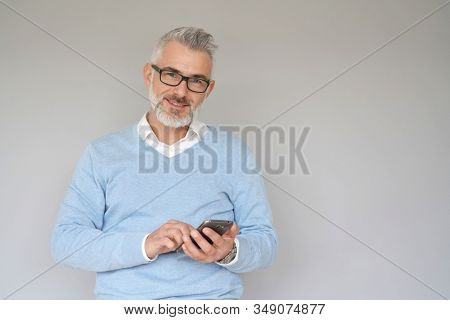 Portrait of middle-aged man using smartphone, isolated