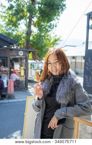 Asian Girl With Dango With Sauce. Dango Made From Japanese Rice And One Of Sweet Japan Snack.