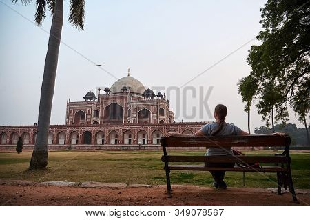 Young Woman Sitting At A Bench And Lookin To Humayuns Tomb Is The Tomb Of The Mughal Emperor Humayun