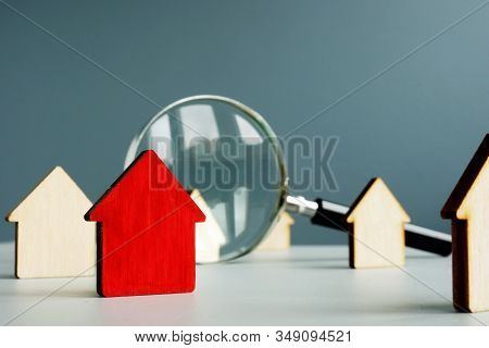 Home Worth And Property Value Concept. Magnifying Glass And Model Of House.