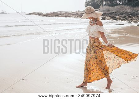 Girl wearing floral maxi skirt walking barefoot on the sea shore, Thailand, Phuket. Bohemian clothing style.