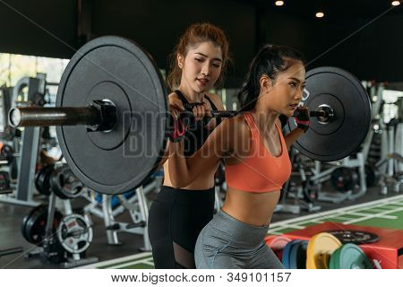 Asian Personal Trainer Coaching A Bodybuilding Woman To Perform The Exercise Squat With Barbell In T