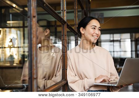 Image of young beautiful asian woman smiling and holding laptop computer while working in office