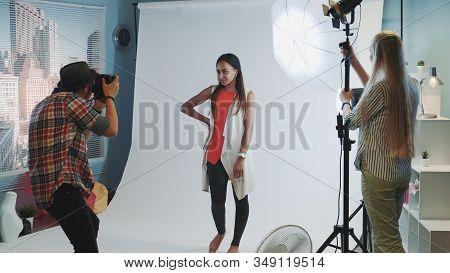 Behind The Scenes On Photo Shoot: Photographer Asking Assistant To Direct The Lighting To The Model.
